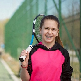 A young girl on a tennis court holding a racquet