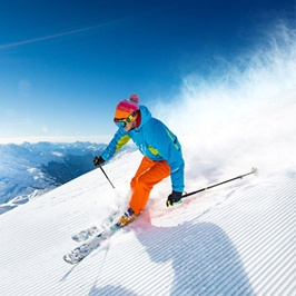 A person skiing down a mountain while the sun is shining