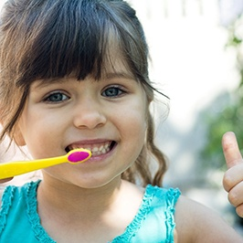 Girl with toothbrush giving thumbs up for fighting cavities