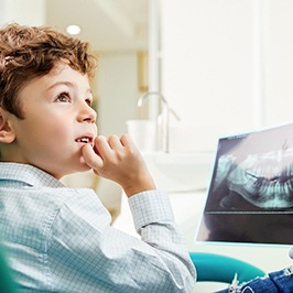 Young male dental patient discussing X-ray with dentist