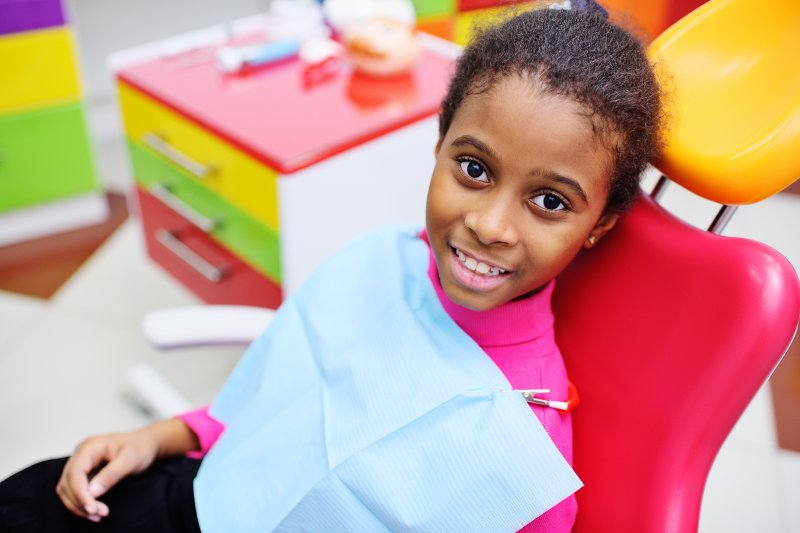 a little girl in the dentist's chair smiling